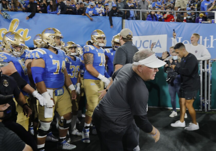UCLA coach Chip Kelly runs on to the field before a game.