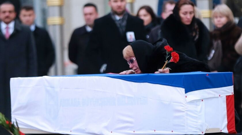Marina Davydova Karlova, widow of Russian Ambassador to Turkey Andrei Karlov, weeps over his coffin during a ceremonial farewell on the tarmac of Ankara's Esenboga Airport on Dec. 20, 2016.