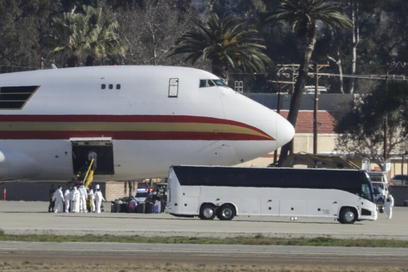 Workers in hazmat suits remove luggage and other cargo from the chartered jet that brought American evacuees from Wuhan, China, to March Air Reserve Base on Jan. 29.