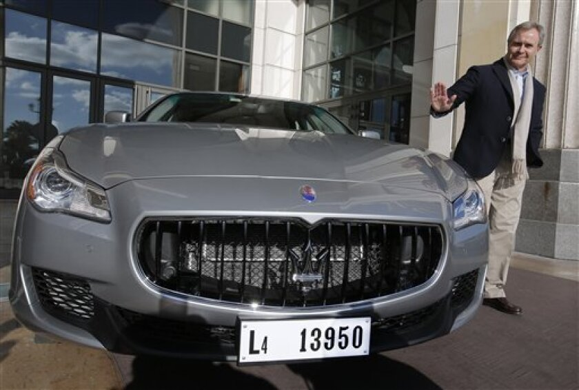 CEO of Maserati Harald Wester poses for photographers next to a new Maserati Quattroporte in Nice, southern France, during a presentation to the media, Monday, Dec. 10, 2012. The new sixth-generation Maserati Quattroporte is a luxury four-door saloon made by Maserati in Italy and will be shown at the Detroit motor show in January 2013, production started in November 2012. (AP Photo/Lionel Cironneau)