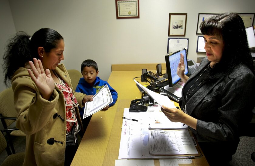 Aurea Mendez Martinez, left, recites the oath of citizenship for her son, seven-year-old Jesus Maldonado, center. The oath was administered in April 2013 by immigration services officer Martha Chi, right, at the Chula Vista U.S. Citizenship and Immigration Services office. U-T San Diego file photo.
