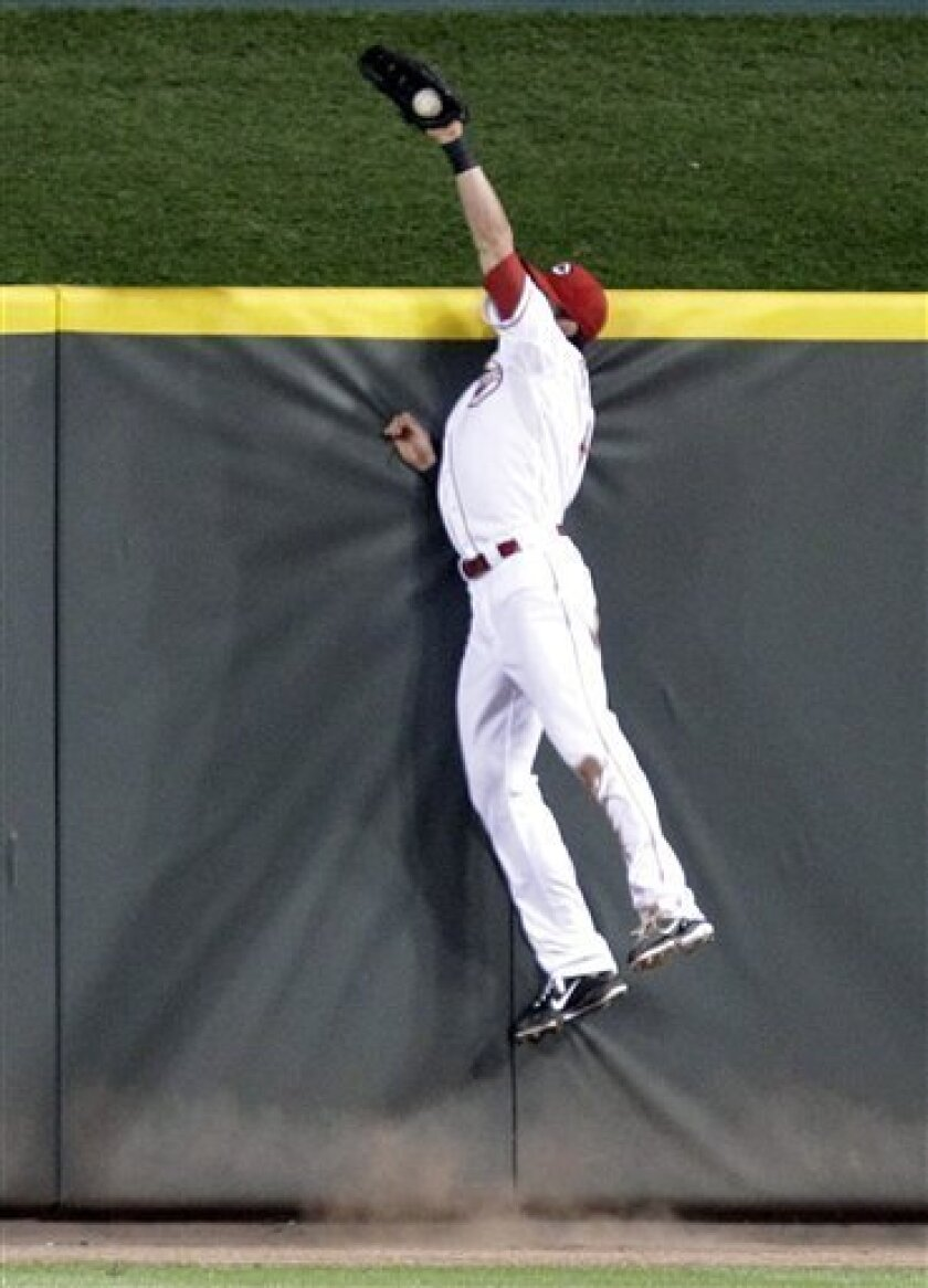 Cincinnati Reds center fielder Drew Stubbs takes a home run away from Houston Astros' Carlos Lee in the third inning of a baseball game Tuesday, Sept. 28, 2010, in Cincinnati. (AP Photo/Al Behrman)