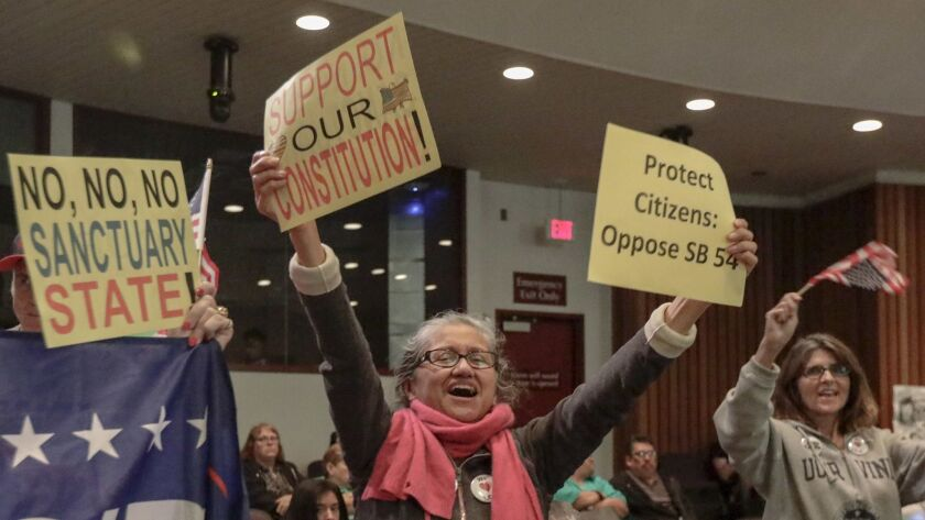 """People celebrate the Orange County Board of Supervisors' resolution Tuesday to condemn California's """"sanctuary"""" laws protecting undocumented immigrants."""