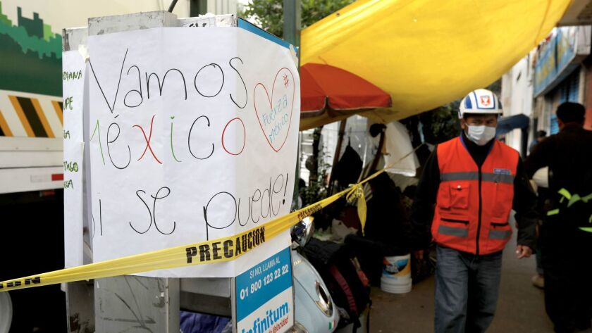 """A sign reads: """"Let's go Mexico. Yes we can,"""" on a payphone near where families camp waiting for news of loved ones as the search for victims continues in Mexico City's Condesa district."""