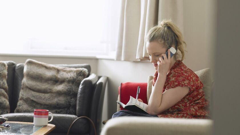 Woman using mobile phone sitting in living room, elevated view
