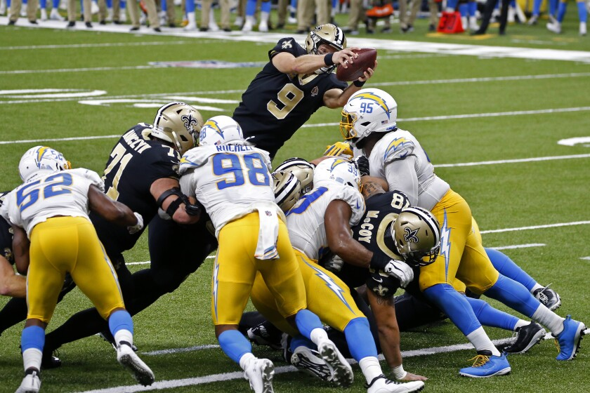 New Orleans Saints quarterback Drew Brees dives over the Chargers' defensive line to score a touchdown.