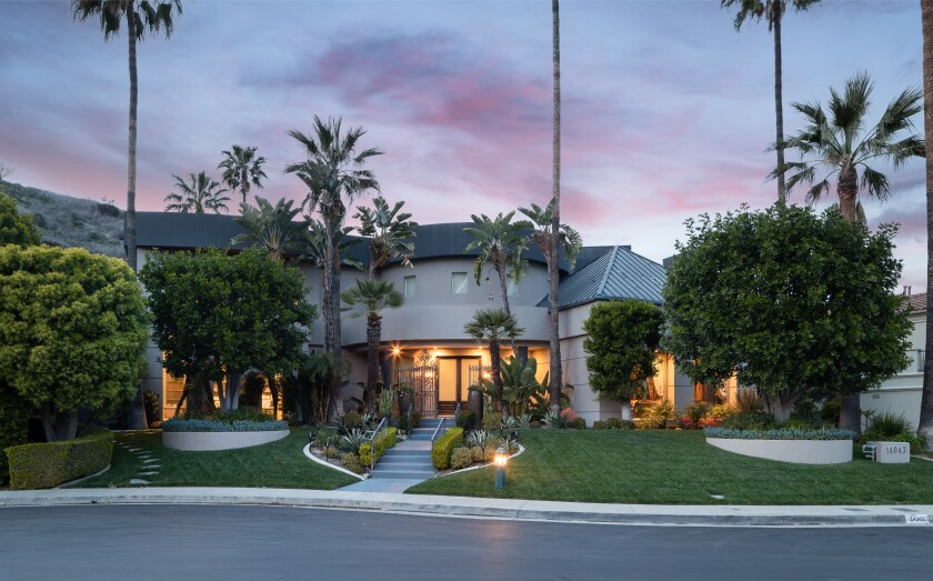 A short walkway leads from the street up to a one-story home with glass doors at twilight