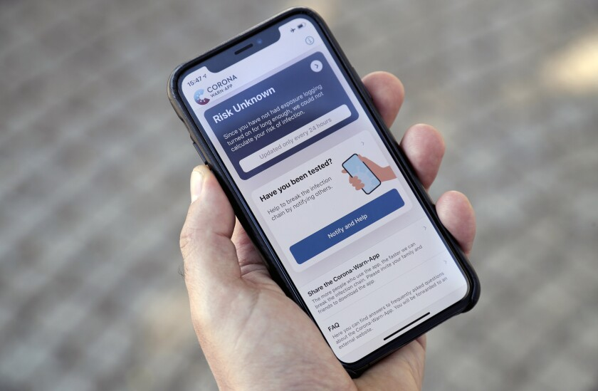 A person holds a smartphone with the official 'Corona Warn-App' (Corona Warning Application) in Berlin, Germany, Monday, June 15, 2020. The app will be introduced on Tuesday, June 16 by the German authorities. (AP Photo/Michael Sohn)