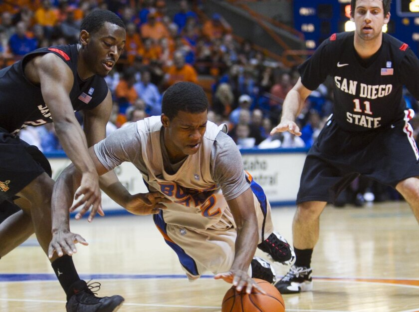 Boise State's Derrick Marks dives onto a loose ball ahead of SDSU's Xavier Thames (left) and James Rahon.