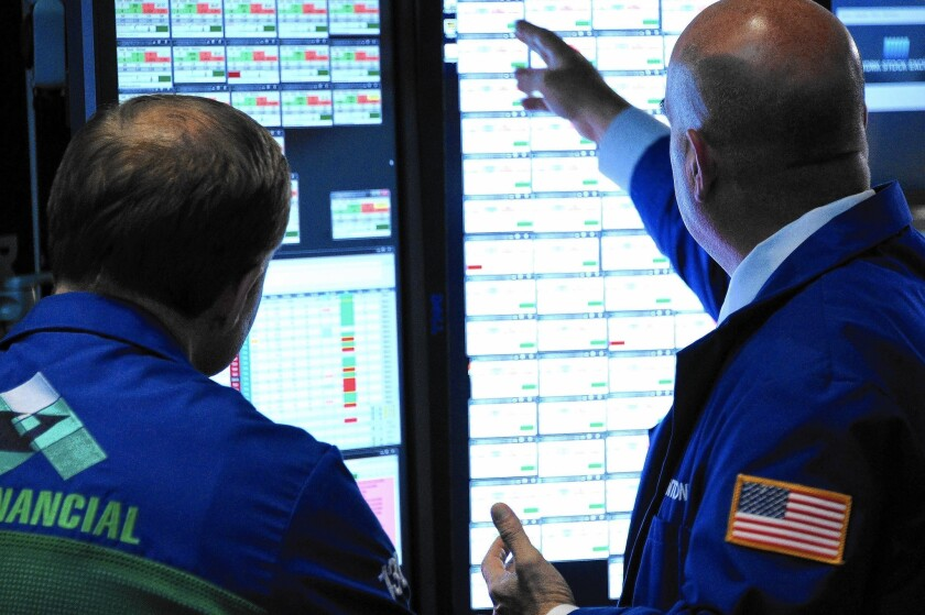 Traders work on the floor of the New York Stock Exchange on Thursday, another volatile trading day.