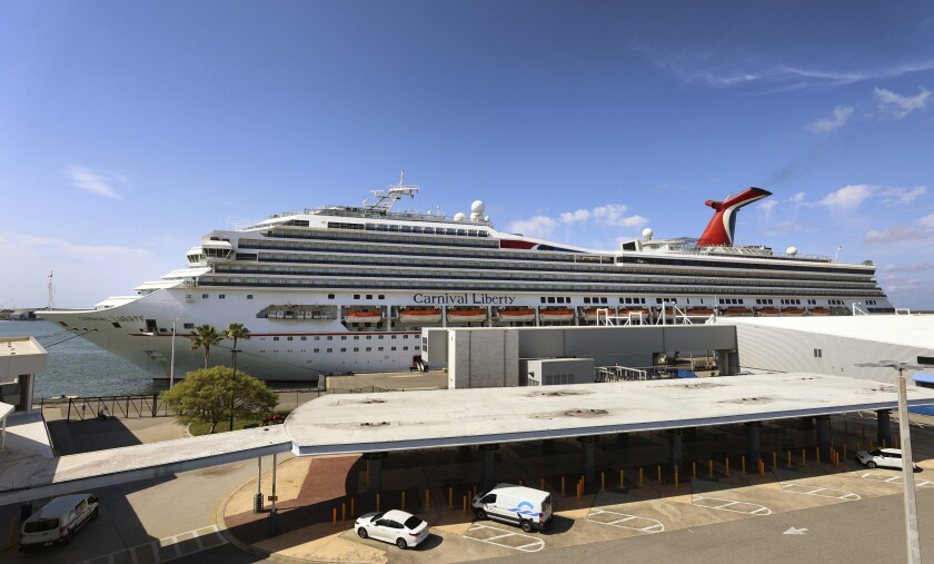 """FILE - In this Wednesday, May 12, 2021, file photo, the Carnival Cruise ship """"Liberty"""" is docked at Port Canaveral, Fla., as crew members get vaccinated for COVID-19. Carnival Corp. is still losing money, but it sees a glimmer of hope in stronger bookings for next year. The cruise line company said Friday, Sept. 24, 2021, that it lost $2.8 billion in the third quarter, which ended Aug. 31. (Joe Burbank/Orlando Sentinel via AP, File)"""