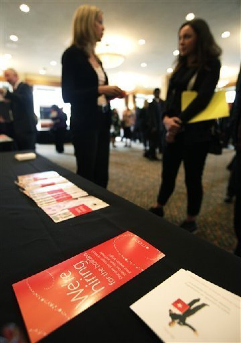 "In this Sept. 14, 2011 photo, a brochure from Macy's that reads ""We're hiring for the holidays,"" is shown at a National Career Fairs job fair, in Bellevue, Wash. The number of people applying for unemployment benefits was little changed last week, evidence that the job market isn't getting much better. (AP Photo/Ted S. Warren)"