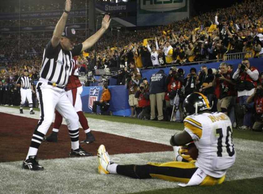 Steelers receiver Santonio Holmes, sitting in the end zone as the referee signals, clutches the football after making a game-winning touchdown catch against the Cardinals in Super Bowl XLIV.