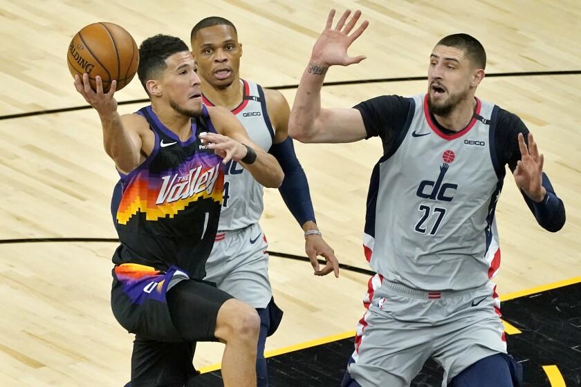 Phoenix Suns guard Devin Booker (1) drives as Washington Wizards center Alex Len (27) defends during the first half of an NBA basketball game, Saturday, April 10, 2021, in Phoenix. (AP Photo/Matt York)