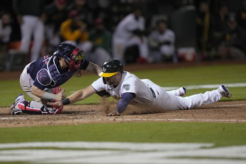 Boston Red Sox catcher Christian Vazquez tags out Oakland Athletics' Seth Brown at home plate during the 10th inning of a baseball game Friday, July 2, 2021, in Oakland, Calif. (AP Photo/Tony Avelar)