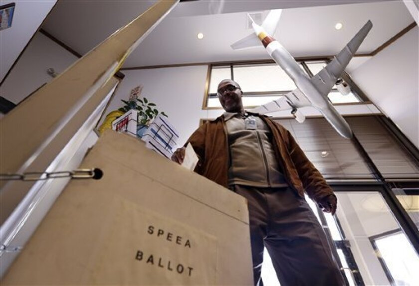 With a model 757 over his shoulder, Ernest Griffin drops his ballot at the headquarters of the union for Boeing Co.'s engineers and technical workers, Tuesday, Feb. 19, 2013, in Tukwila, Wash. Members of the Society of Professional Engineering Employees in Aerospace (SPEEA) are voting on a contract