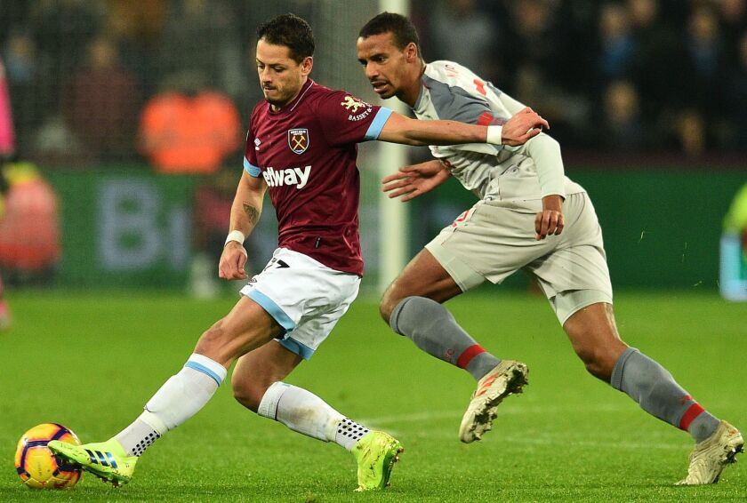 West Ham United's Mexican striker Javier Hernandez (L) pulls away from Liverpool's German-born Cameroonian defender Joel Matip during the English Premier League football match between West Ham United and Liverpool at The London Stadium, in east London on February 4, 2019.