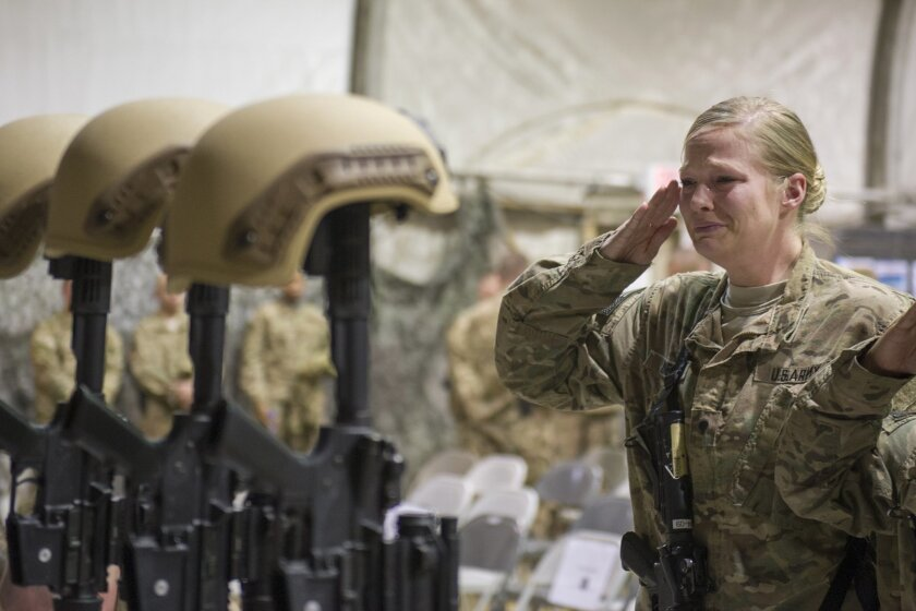 A U.S. service member salutes her fallen comrades after six were killed in Afghanistan.