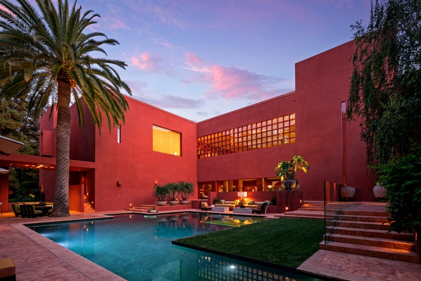 Blockbuster filmmaker Joel Silver has listed his Brentwood home for sale at $77.5 million. The Mexican modernist residence was designed by architect Ricardo Legorreta and completed in the early 2000s. Features of the 26,000-square-foot house include a circular atrium and a grand dining room with a pyramid-like ceiling.