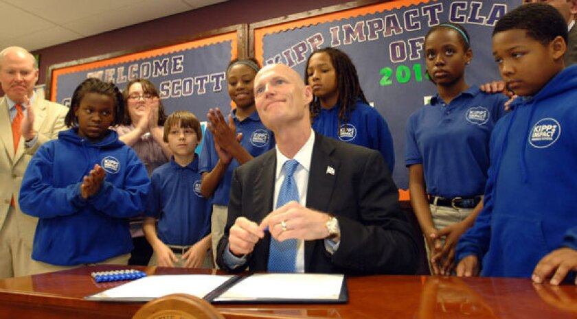 Florida Gov. Rick Scott signs his controversial teacher-merit pay law, surrounded by Kipp Middle School students in Jacksonville.