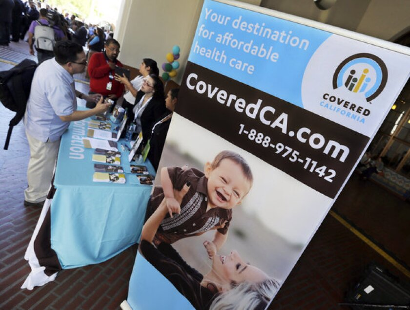 An information table is busy at Union Station in downtown Los Angeles on Oct. 1 as people seek information on health insurance sold through Covered California, the state's new marketplace for coverage.