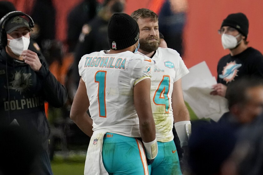 Miami Dolphins quarterback Tua Tagovailoa (1) talks with quarterback Ryan Fitzpatrick (14) during the final seconds of an NFL football game against the Denver Broncos, Sunday, Nov. 22, 2020, in Denver. The Broncos won 20-13. (AP Photo/David Zalubowski)