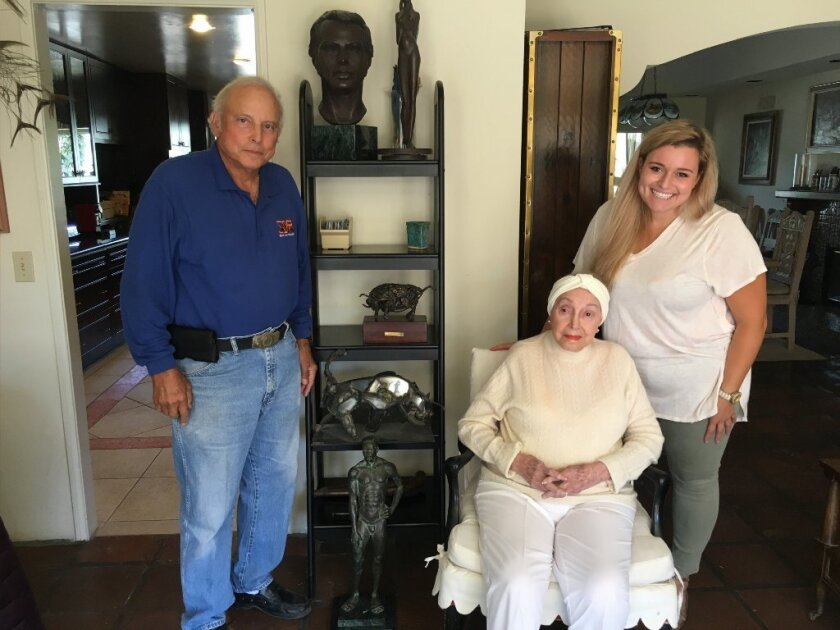 Marian Snyder sits in front of some of her sculptures along with her son Martin Buncher and granddaughter Lizzie. Snyder turned 102 last month.