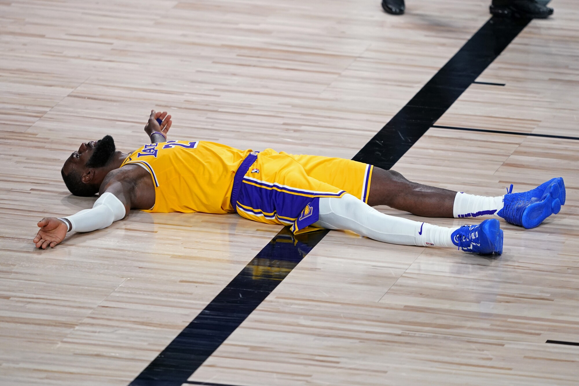 Lakers forward LeBron James lies on the court after committing a foul during the second half.