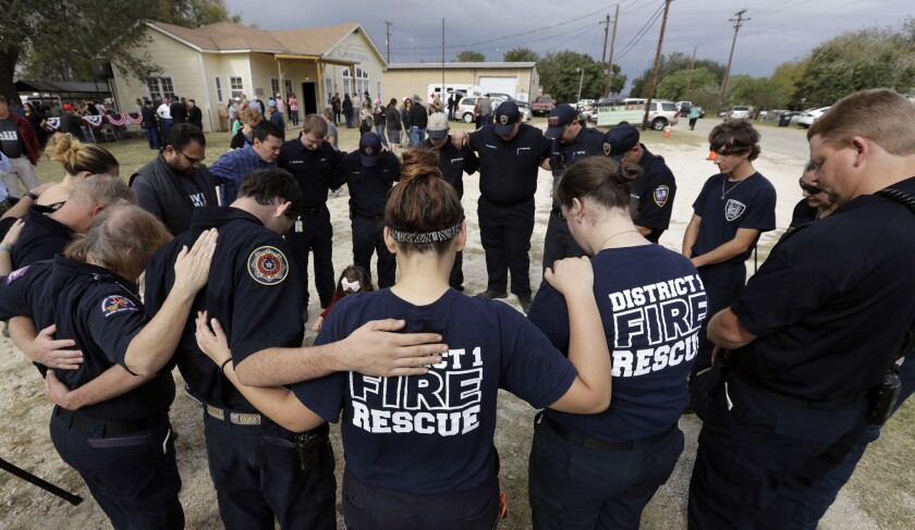 First responders join in prayer following a Veterans Day event, Saturday, Nov. 11, 2017, near the Su