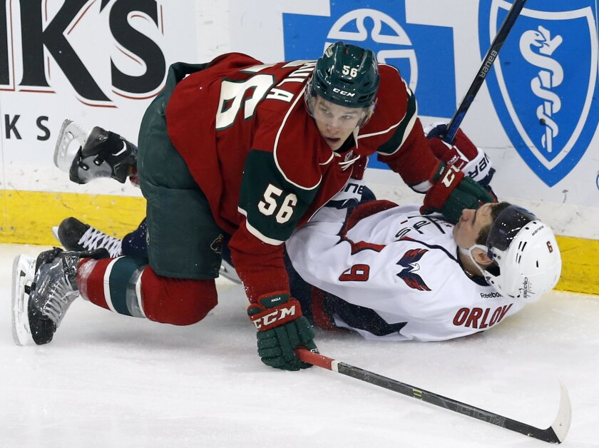 Washington Capitals' Dmitry Orlov, right, of Russia, hits the ice courtesy of Minnesota Willd's Erik Haula of Finland in the first period of an NHL hockey game, Thursday, Feb. 11, 2016, in St. Paul, Minn. (AP Photo/Jim Mone)