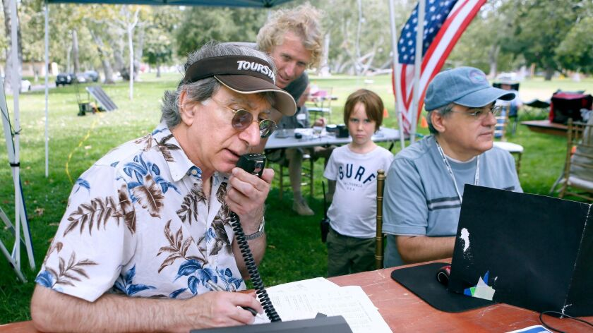 While ham radio hobbyist Rob Hoegee, rear left, and his six-year old son Henry look on, Crescenta Valley Radio Club member Steve Burkholder logs finds at right, and fellow member Bob Cesarone, left, makes contact with another group at Verdugo Park on June 24, 2017.
