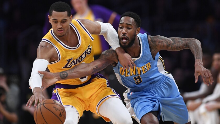 Lakers guard Jordan Clarkson, left, and Denver Nuggets guard Will Barton reach for a loose ball during the first half.