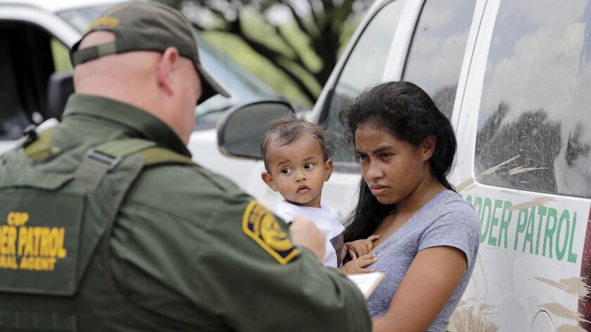 A mother migrating from Honduras holds her 1-year-old child while surrendering to U.S. Border Patrol agents on June 25 after authorities said she illegally crossed the border, near McAllen, Texas.