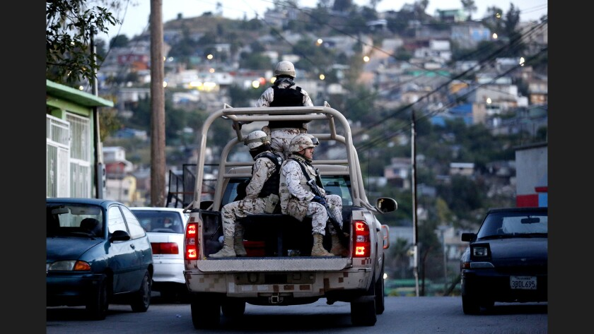 Mexican soldiers leave the scene of a homicide in Baja California in April.
