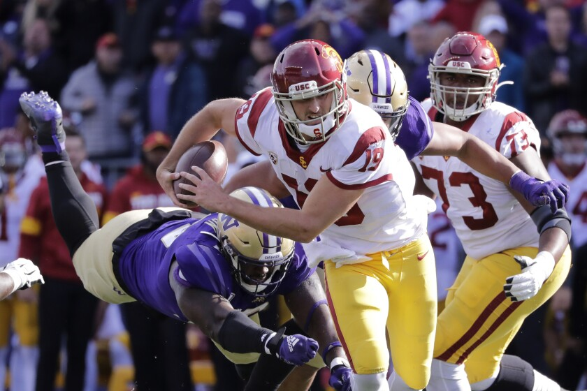 USC quarterback Matt Fink carries the ball as Washington's Josiah Bronson tumbles behind in the second half on Saturday in Seattle. Washington won 28-14.