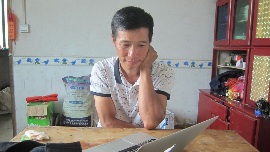 Zeng Youdong looks at a laptop