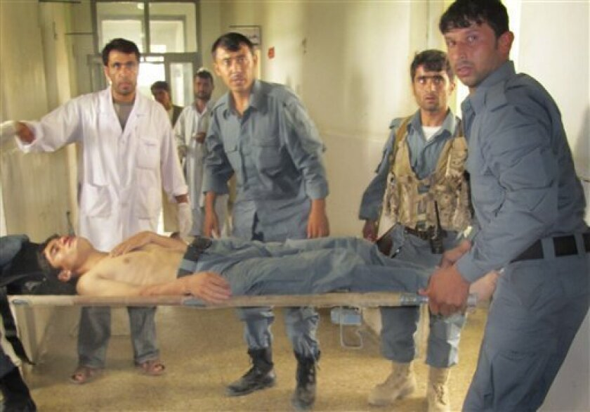 Police officers carry an injured Afghan police officer on a stretcher at a hospital in Kunduz city, in the northern province of Kunduz, Afghanistan, Friday, June 10, 2011. A suicide bomber blew himself up outside a mosque where a remembrance ceremony was being held Friday for a top Afghan police commander, killing four police officers and wounding several others authorities said.(AP Photo/Fulad Hamdard)