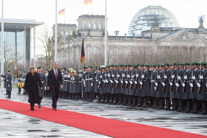 German Chancellor Angela Merkel and visiting NATO chief Jens Stoltenberg review military honors in Berlin on Jan. 14.