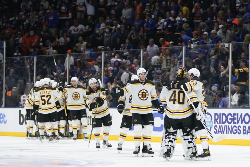 Boston Bruins goaltender Tuukka Rask (40) celebrates with Charlie McAvoy (73) and other teammates after Game 3 during an NHL hockey second-round playoff series against the New York Islanders Thursday, June 3, 2021, in Uniondale, N.Y. The Bruins won 2-1. (AP Photo/Frank Franklin II)
