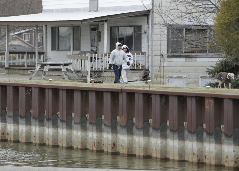 FILE - In this March 23, 2015, file photo, a couple walks their dog along the 4.1-mile earthen dam at Buckeye Lake in Buckeye Lake, Ohio. Water levels have been kept low at the Central Ohio lake because of the deteriorated dam, which is nearly 180 years old, but state officials said Thursday, May 2