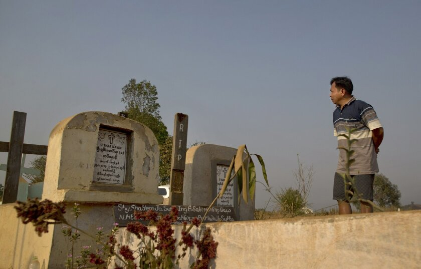 In this March 21, 2015, photo, Brang Shawng weeps during a visit to the grave of his daughter Ja Seng Ing, who was killed in what witnesses say was a burst of army gunfire in Hpakant Christian cemetery, Northern Kachin state, Myanmar. After hearing of his country's move towards a new civilian democ