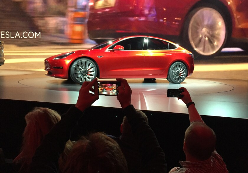 Tesla Motors unveiled its popular-priced Model 3 electric car to great excitement Thursday, but the real thing won't be available until late next year, if then.