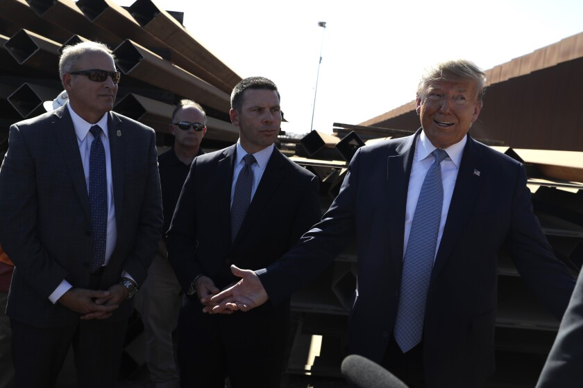 President Donald Trump talks with reporters as he tours a section of the southern border wall, Wednesday, Sept. 18, 2019, in Otay Mesa, Calif., as acting commissioner of Customs and Border Protection Mark Morgan, left, and acting Homeland Secretary Kevin McAleenan listen. (AP Photo/Evan Vucci)