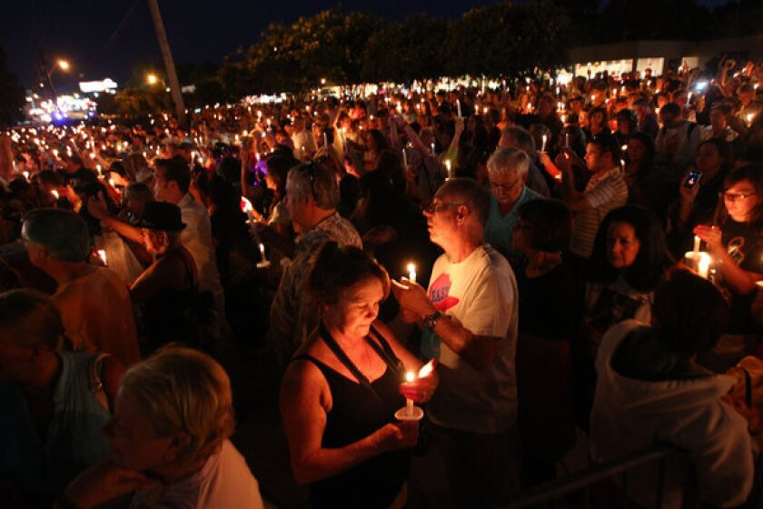 Fans of the late Elvis Presley gather at Graceland, the performer's home, for a candlelight vigil on Aug. 15, 2013, in Memphis, Tenn.