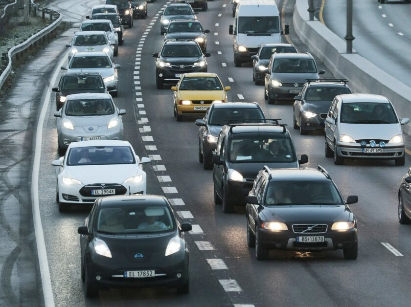 FILE - In this Nov. 26, 2014 file photo electric cars queuie in the bus lane, left, on the main road to Oslo. Norway wants to get rid of gasoline-fueled cars, plans to become carbon neutral by 2030 and spends billions on helping poor countries reduce their carbon footprints. Meanwhile, it's pushing