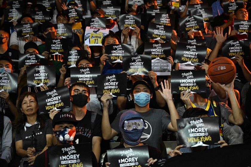 Protesters shout slogans as they hold flyers during a rally in Hong Kong in support of Rockets general manager Daryl Morey on Tuesday.