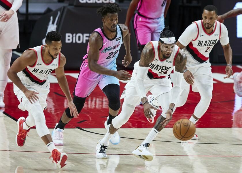 El jugador de los Trail Blazers Robert Covington, segundo por la derecha, lidera una ofensiva con CJ McCollum, a la izquierda, y Norman Powell, a la derecha, seguidos por el jugador del Heat de Miami Jimmy Butler, en la segunda mitad de su juego de NBA en Portland, Oregon, el domingo 11 de abril de 2021. (AP Foto/Craig Mitchelldyer)