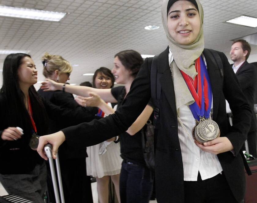 Senior Hamidah Mahmud, a member of Granada Hills Charter High School's national champion Academic Decathlon team, shows off her medals after arriving at Los Angeles International Airport. El Camino Real Charter High finished second in the rigorous two-day competition in Minneapolis. It was Granada Hills' third straight national title.