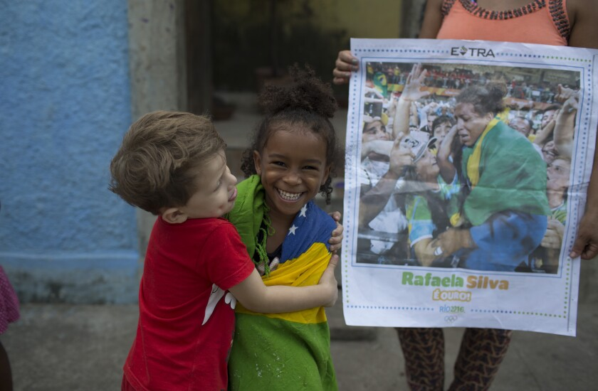 Wrapped in the Brazilian flag, 4-year-old Giovana Silva celebrates the gold medal of her cousin, Rafaela Silva.