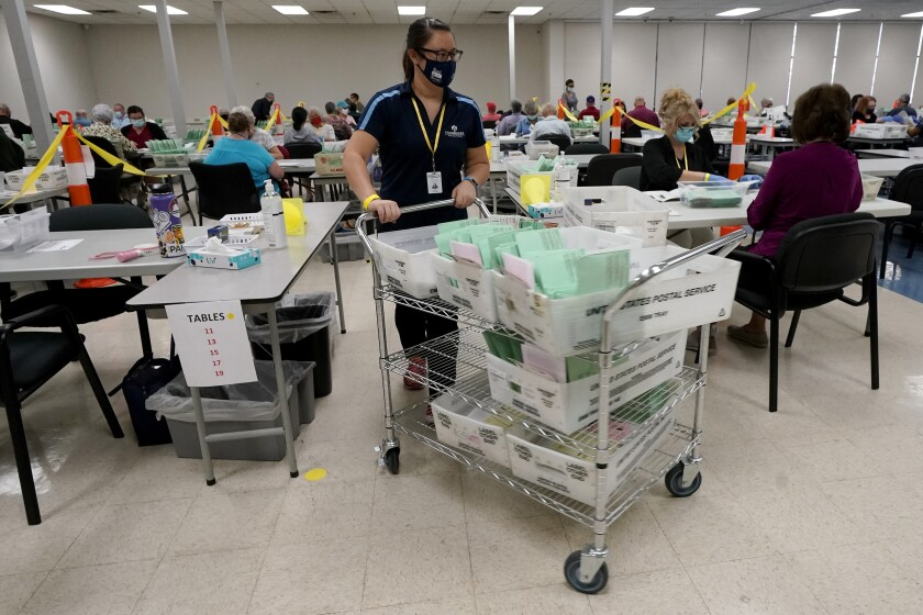 Election workers sort ballots. Gen Zers' ballots figure to account for a respectable portion of those ballots, experts say.